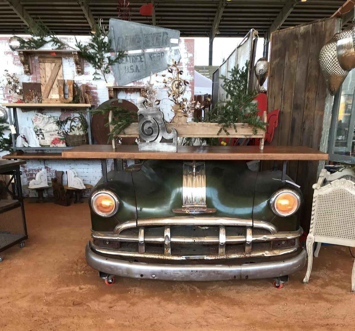 Vintage truck front bumper with shelf on top with bookend on top and Christmas decorations