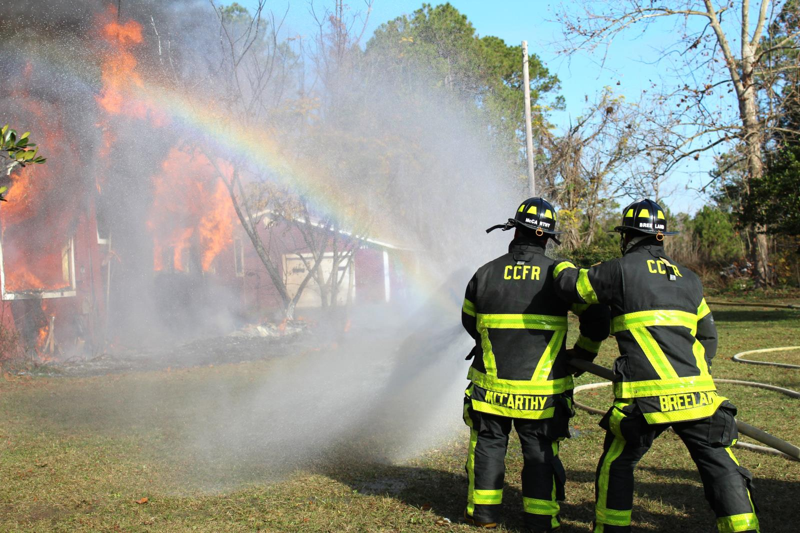 Two firefighters using the firehose to put out a fire with rainbow in the water