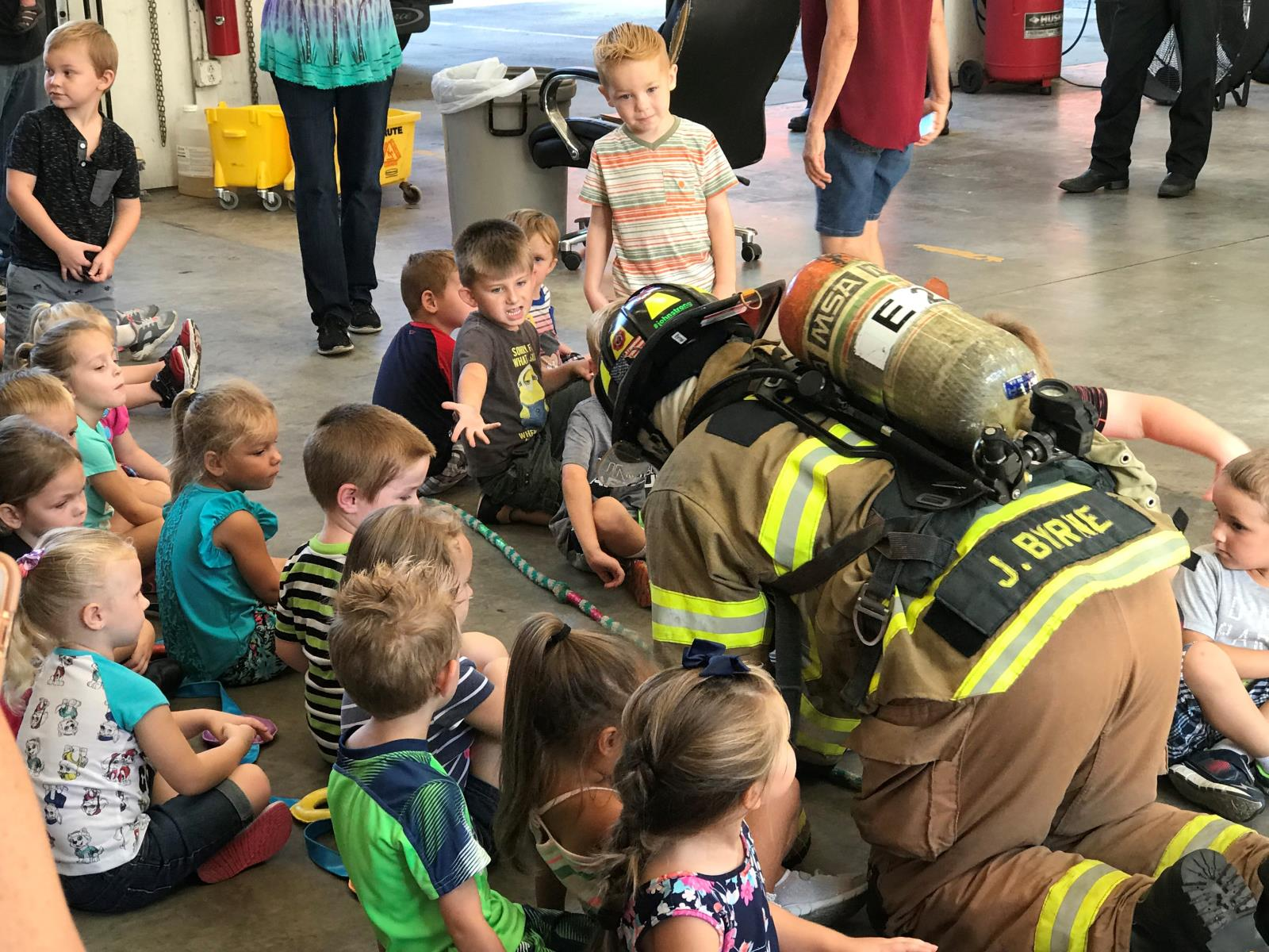 Firefighter crawling on floor in full gear around kids during visit