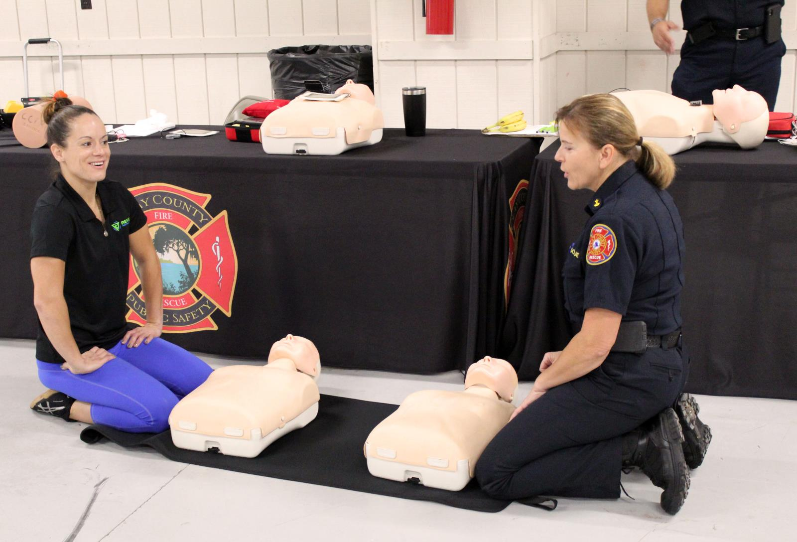 Firefighter on floor demonstrating CPR on dummies