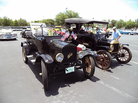 Model T1 vehicles in a parking lot with American flags on the front