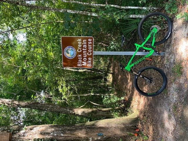 Mountain bike propped against a sign in front of trail