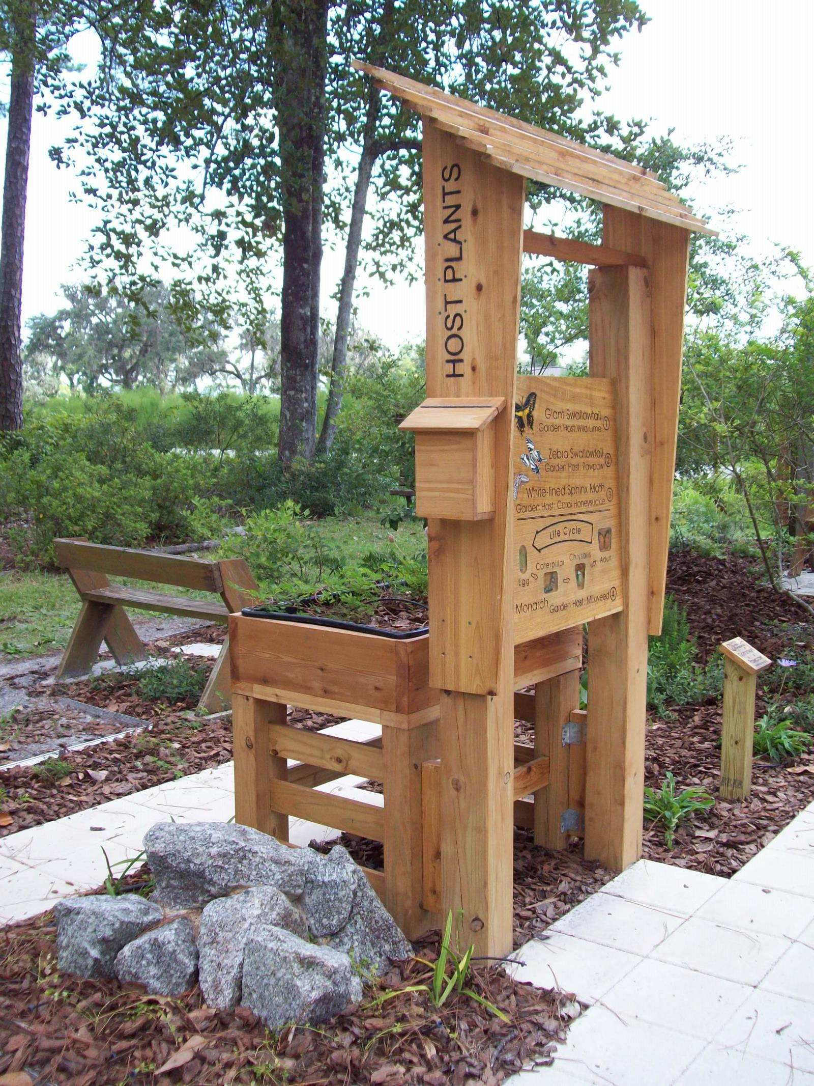 Pollinator kiosk with a bench, rock, sidewalk, and raised flower bed