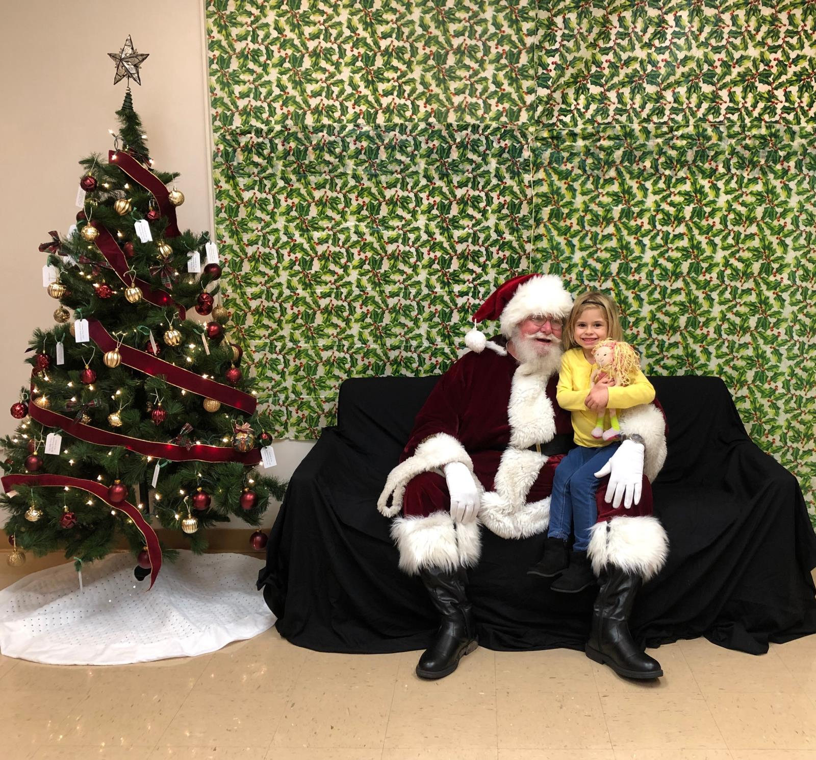 Santa Claus with little girl in yellow on his lap sitting on a couch next to a decorated and lit tree with a green backdrop