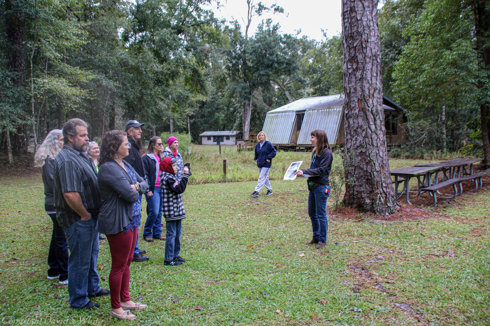 park naturalist explaining to a group in front of a tree and cabins, one child taking a photo in group