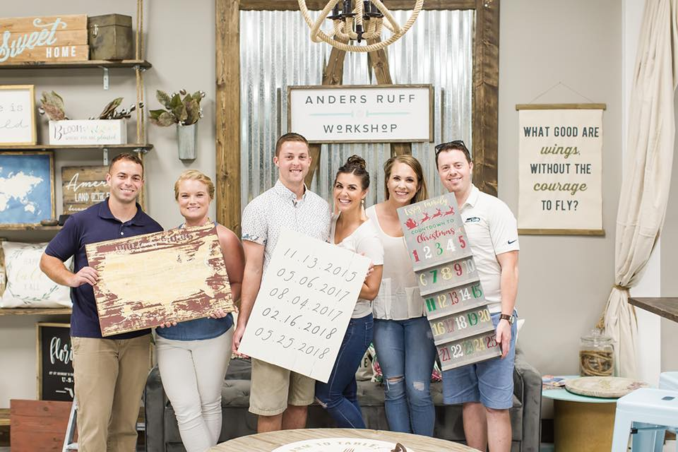 3 couples with their wooden sign designs from workshop